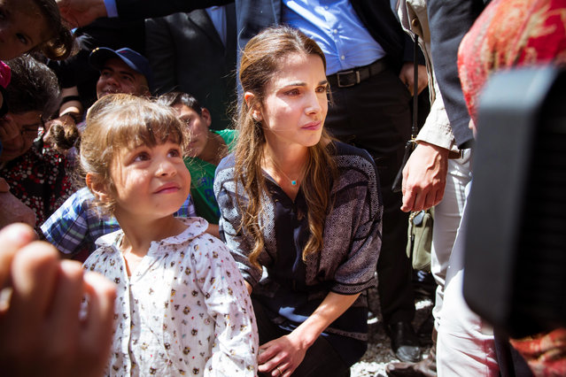 In this picture provided by the Office of Her Majesty's Press Department, Queen Rania of Jordan, center, listens to refugees and migrants during her visit to Kara Tepe municipality camp in the Greek island of Lesbos, Monday, April 25, 2016. (Photo by Office of Her Majesty Press Department via AP Photo)