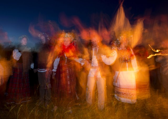 Belarusian people dance as they take part in the Ivan Kupala festival near the town of Rakov, west of Minsk June 27, 2015. (Photo by Vasily Fedosenko/Reuters)