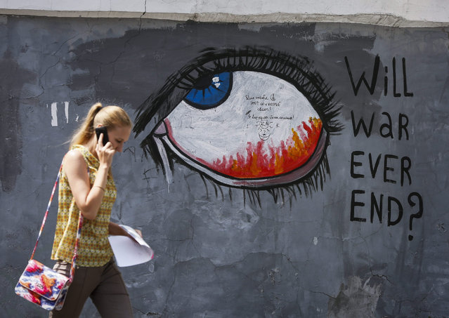 """A woman walks next to graffiti reading """"Will war ever end?"""" in downtown Kiev, Ukraine, 30 June 2015. More than 6,000 people have been killed in eastern Ukraine since pro-Russian rebels and the Ukrainian military began battling in April last year, according to United Nations estimates. (Photo by Roman Pilipey/EPA)"""