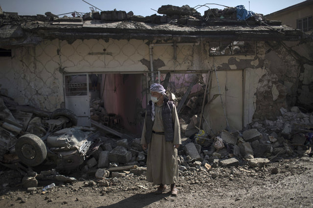 A man stands outside houses damaged during fights between Iraq security forces and Islamic State on the western side of Mosul, Iraq, Friday, March 24, 2017. (Photo by Felipe Dana/AP Photo)