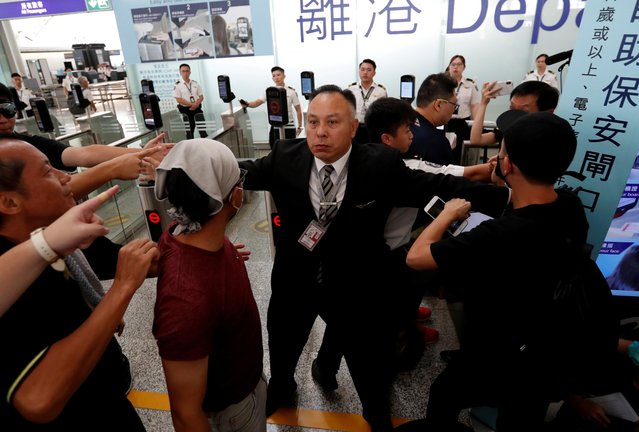 A member of the airport staff tries to stop anti-government protesters during a demonstration at Hong Kong Airport, China on August 13, 2019. (Photo by Issei Kato/Reuters)