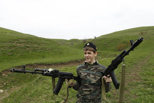 A student from the General Yermolov Cadet School holds two rifles during a two-day field exercise near the village of Sengileyevskoye, just outside the south Russian city of Stavropol, April 13, 2014. (Photo by Eduard Korniyenko/Reuters)