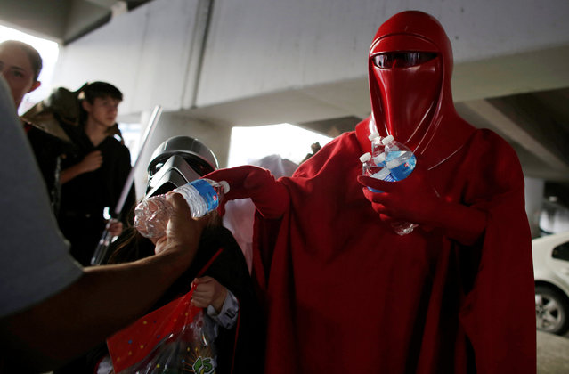 A member of a Star Wars fan club in Mexico, dressed as an Emperor's Royal Guard, gives bottles of water to relatives of patients outside a hospital's emergency ward during Star Wars Day celebration in Monterrey, Mexico May 4, 2016. (Photo by Daniel Becerril/Reuters)