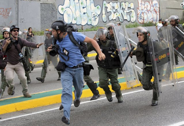 Reuters photojournalist Marco Bello runs as Venezuelan National Guard soldiers chase him during a protest outside the Supreme Court in Caracas, Venezuela, Friday, March 31, 2017. Security forces violently repressed small protests that broke out in Venezuela's capital Friday after the government-stacked Supreme Court gutted congress of its last vestiges of power, drawing widespread condemnation from foreign governments. (Photo by Ariana Cubillos/AP Photo)