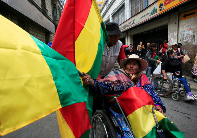 A demonstrator with physical disabilities, holding Bolivia's national flags, participates in a rally protest calling on the government to increase their monthly disability subsidy, in La Paz, Bolivia, May 5, 2016. (Photo by David Mercado/Reuters)