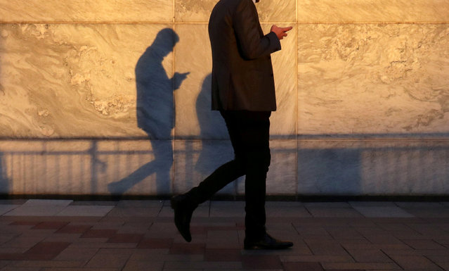 An unidentified man using a smart phone walks through London's Canary Wharf financial district in the evening light in London, Britain, September 28, 2018. (Photo by Russell Boyce/Reuters)