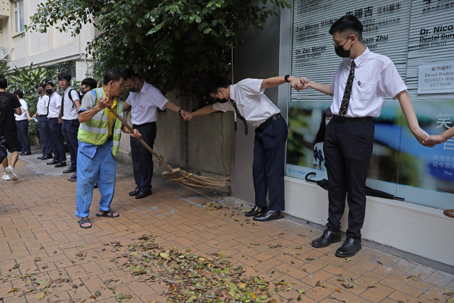 A worker sweeps a road as students hold hands to surround St. Paul's College in Hong Kong, Monday, September 9, 2019. (Photo by Kin Cheung/AP Photo)