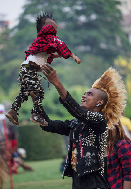 A member of a punk group plays with his one-year-old son as he and some of his friends gather in a park in central Yangon on April 12, 2017, on the eve of the water festival known as Thingyan. (Photo by Roberto Schmidt/AFP Photo)