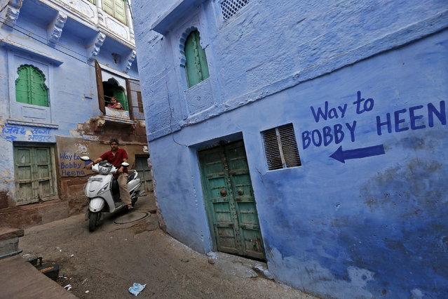 A man rides a scooter through an alley as a woman watches at Jodhpur in Rajasthan, April 5, 2015. (Photo by Adnan Abidi/Reuters)