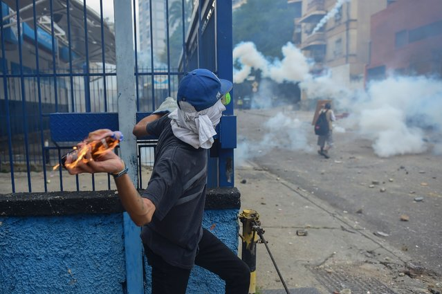 A demonstrator clashes with the police during a rally against Venezuelan President Nicolas Maduro, in Caracas on April 19, 2017. Venezuela braced for rival demonstrations Wednesday for and against President Nicolas Maduro, whose push to tighten his grip on power has triggered waves of deadly unrest that have escalated the country's political and economic crisis. (Photo by Ronaldo Schemidt/AFP Photo)