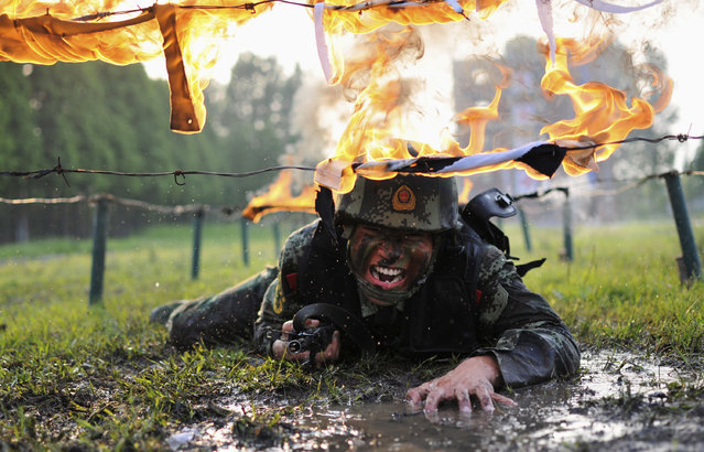 A paramilitary policeman crawls under fire obstacles during a drill at a military base in Chaohu, Anhui province May 5, 2014. (Photo by Reuters/China Daily)