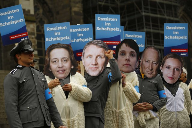 """Members of Avaaz (a global web movement) protest in Third Reich's Wehrmacht uniforms and face masks of L-R Beatrix von Storch, Bjoern Hocke, Frauke Petry, Alexander Gauland and Alice Weidel of Germany's anti-immigration party Alternative for Germany (AFD) under the motto """"wolf in sheep's clothing"""" before the AFD's party congress in Cologne, Germany, April 21, 2017. (Photo by Wolfgang Rattay/Reuters)"""