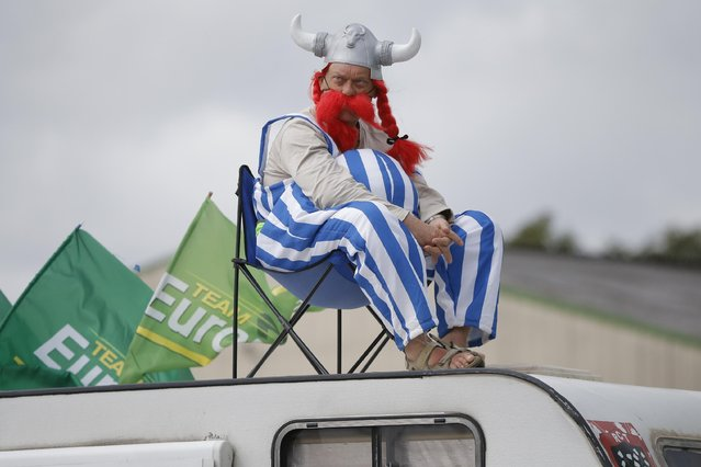 A spectator watches teams during the ninth stage of the Tour de France cycling race, a team time-trial over 28 kilometers (17.4 miles) with start in Vannes and finish in Plumelec, France, Sunday, July 12, 2015. (Photo by Laurent Cipriani/AP Photo)