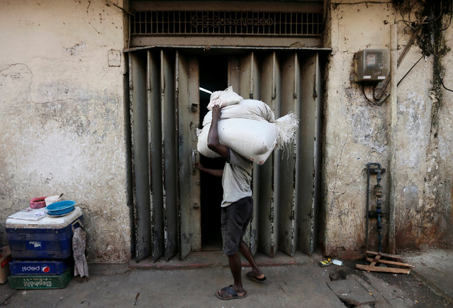 A labourer tries to open a door at a store room as he carries sacks of rice near a main market in Colombo, Sri Lanka February 21, 2017. (Photo by Dinuka Liyanawatte/Reuters)