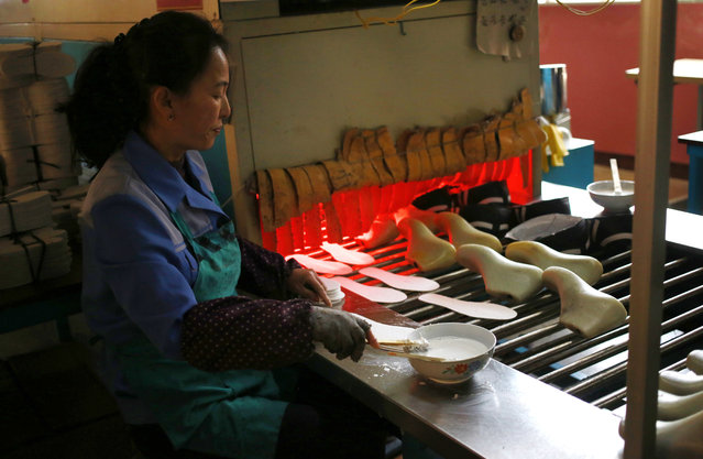 In this Friday, February 1, 2019, photo, a worker tend to her station at Ryuwon Shoe Factory that specializes in sports footwear, in Pyongyang, North Korea. North Korean pop culture, long dismissed by critics as a kitschy throwback to the dark days of Stalinism, is getting a major upgrade under leader Kim Jong Un. The changes are being seen in everything from television dramas and animation programs to the variety and packaging of consumer goods, which have improved significantly under Kim. (Photo by Dita Alangkara/AP Photo)