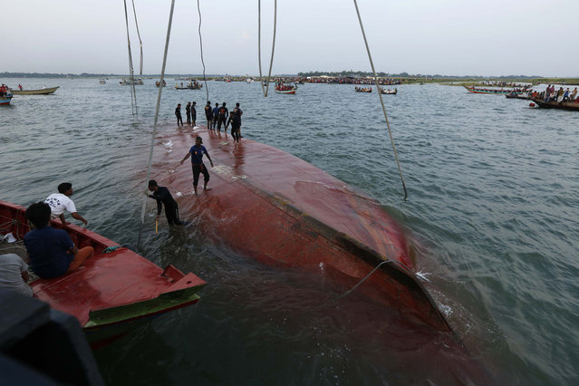 Rescue workers stand on the partially salvaged M.V. Miraj-4 ferry after it capsized on the Meghna river at Rasulpur in Munshiganj district May 16, 2014. A Bangladeshi official said on Friday there was no chance of finding further survivors of a ferry that sank in a storm with about 200 people on board, the latest in a series of fatal ferry accidents to hit the poverty-stricken country. (Photo by Andrew Biraj/Reuters)