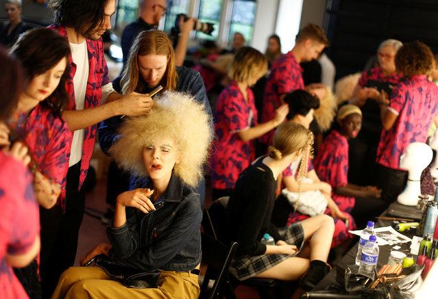 Hairstylists work on models backstage before a fashion show for the label Romance Was Born on the waterfront of Sydney Harbour during Australian Fashion Week, Sydney, Australia May 18, 2016. (Photo by Jason Reed/Reuters)