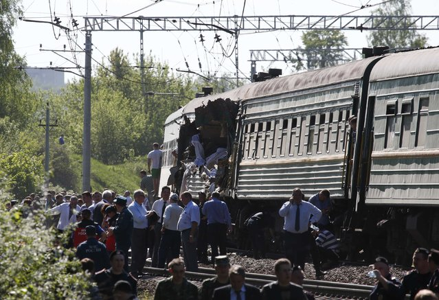 People gather near a passenger train damaged in a collision with a freight train in Moscow region May 20, 2014. The passenger train on its way to Moldova collided with a freight train near Moscow on Tuesday, killing at least four people and injuring 15, a spokeswoman for Russia's Emergencies Ministry said. The reason for the collision, near the town of Naro-Fominsk 55 km (34 miles) southwest of Moscow, was not immediately clear. (Photo by Grigory Dukor/Reuters)