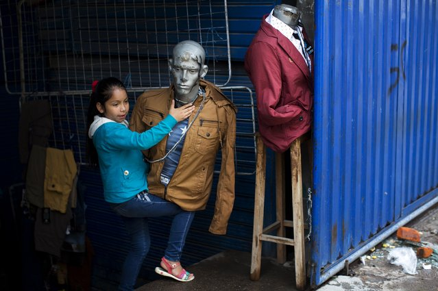 A girl arranges a mannequin at a shop, a day after general elections were held, at the central market in Ayacucho, Peru, Monday, April 11, 2016. (Photo by Rodrigo Abd/AP Photo)