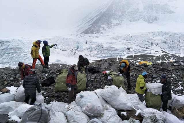 In this Monday, May 8, 2017 photo released by Xinhua News Agency, people collect garbage at the north slope of the Mount Qomolangma in southwest China's Tibet Autonomous Region. Workers and volunteers collected four tons of garbage from the Chinese north side of Mount Everest in the first five days of a cleanup operation, state media reported Thursday, May 11, 2017. (Photo by Awang Zhaxi/Xinhua via AP Photo)