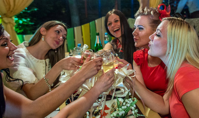 Young women celebrate a birthday at a Donetsk nightspot, on May 23, 2014. Polls show that most young people in Ukraine – a quarter of the population is 24 or younger – do not blur the boundaries between themselves and their powerful neighbor, even if they disagree about how best to relate to Russia, a crucial economic lifeline for many in Ukraine's industrial east. (Photo by Evelyn Hockstein/The Washington Post)
