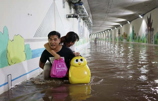 A man carries his wife on his back as they make their way with their luggage along a flooded tunnel to catch their train, after heavy rainfall hit Jinhua, Zhejiang province, China, July 21, 2015. (Photo by Reuters/China Daily)