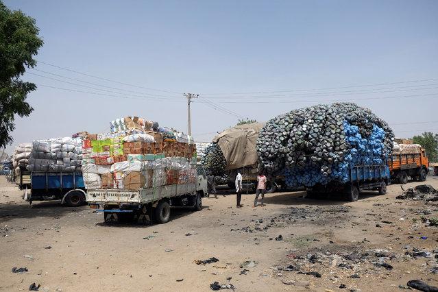 Two men stand between trucks laden with goods in Muna Garage area Maiduguri, Nigeria February 16, 2017. (Photo by Paul Carsten/Reuters)
