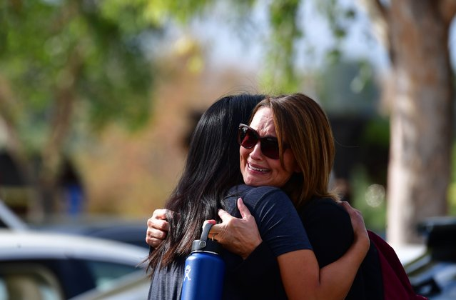 """Grieving students from Saugus High School reunite with their parents at Central Park in Santa Clarita, California, on November 14, 2019. A teenage boy gunned down fellow students at a California high school on his 16th birthday Thursday, killing two and wounding another three before turning the pistol on himself. The gunman was taken into custody in """"grave"""" condition, police said, as officers stormed Saugus High School in Santa Clarita – the latest in a relentless cycle of classroom shootings that have left around 300 youngsters dead over two decades. (Photo by Frederic J. Brown/AFP Photo)"""