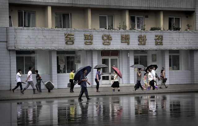 People carry umbrellas as they walk past a department store, Saturday, July 25, 2015, in Pyongyang, North Korea. The rainy season in North Korea usually lasts through the month of July. (Photo by Wong Maye-E/AP Photo)