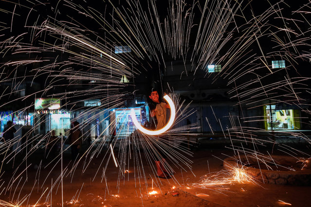 A Palestinian plays with fire crackers as he celebrates the Muslim holy month of Ramadan at the town of Rafah in the southern Gaza Strip, on June 2, 2017. Ramadan is sacred to Muslims because it is during that month that tradition says the Koran was revealed to the Prophet Mohammed. The fast is one of the five main religious obligations under Islam. More than 1.5 billion Muslims around the world will mark the month, during which believers abstain from eating, drinking, smoking and having s*x from dawn until sunset. (Photo by Said Khatib/AFP Photo)