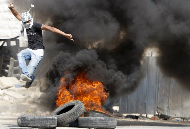 A Palestinian jumps over burning tyres during clashes with Israeli troops in the West Bank city of Hebron July 31, 2015. (Photo by Mussa Qawasma/Reuters)