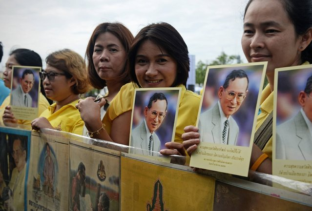 Women pose for cameras whilst holding images of Thailand's King Bhumibol Adulyadej during the commemoration of the 70th anniversary of his reign in Bangkok on June 9, 2016. Thailand marked the 70th anniversary of King Bhumibol's ascension to the throne following the mysterious 1946 death of his brother as anxieties deepen over the increasingly frail health of the hospital-bound monarch. (Photo by Lillian Suwanrumpha/AFP Photo)