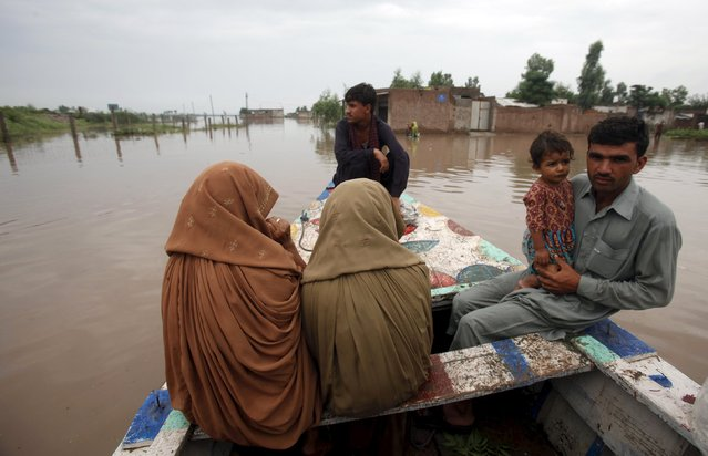 Rescue crews evacuate a family to a safe area in Camp Koruna Akbar in the Pura area of Nowshera District, northwestern Pakistan, August 2, 2015. (Photo by Fayaz Aziz/Reuters)