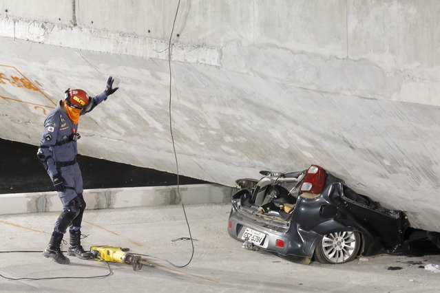 A policeman looks at a car crushed underneath a collapsed bridge in Belo Horizonte, Brazil, Thursday, July 3, 2014. The overpass under construction collapsed Thursday in the Brazilian World Cup host city. The incident took place on a main avenue, the expansion of which was part of the World Cup infrastructure plan but, like most urban mobility projects related to the Cup, was not finished on time for the event. (Photo by Victor R. Caivano/AP Photo)