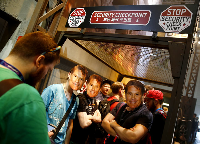 """Visitors wearing David Hasselhoff masks queue to play """"Homefront: The Revolution"""", developed by video game producer Deep Silver during the Gamescom 2015 fair in Cologne, Germany August 5, 2015. (Photo by Kai Pfaffenbach/Reuters)"""