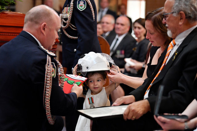 Charlotte O'Dwyer, the daughter of Rural Fire Service volunteer Andrew O'Dwyer, with Andrew's wife Melissa, receives her father's helmet after being presented with her father's service medal by RFS Commissioner Shane Fitzsimmons during the funeral for Andrew O'Dwyer at Our Lady of Victories Catholic Church in Horsley Park, Sydney, Australia, January 7, 2020. (Photo by Dean Lewins/AAP Image/Pool via Reuters)