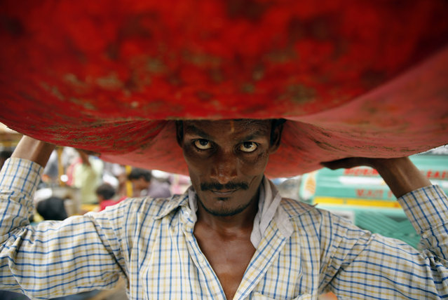 An Indian vendor carries a huge sack of flowers on his head at a wholesale flower market in Lucknow, India, Friday, August 7, 2015. On a good day, the vendor can earn 6 to 8 US dollars. (Photo by Rajesh Kumar Singh/AP Photo)