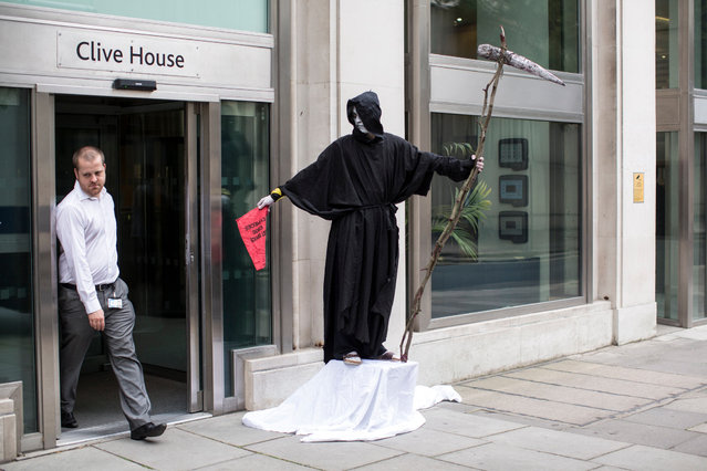 A man dressed as the Grim Reaper stands on a union picket line as he takes industrial action outside the offices for the National Offender Management Service in London, England, on Jule 10, 2014. Over one million public sector workers are expected to take strike action today across the UK over disputes with the Government concerning pay, pensions and cuts. (Photo by Oli Scarff/Getty Images)