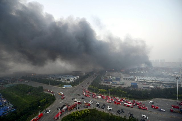 Firefighter's truck and other rescue vehicles are pictured as smoke rises among shipping containers after explosions at Binhai new district in Tianjin, China, August 13, 2015. (Photo by Reuters/Stringer)