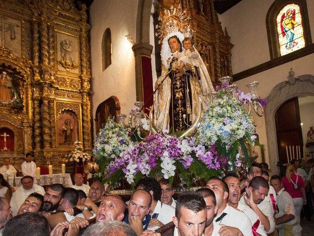 Penitents carry the Virgen del Carmen, the patron saint of fishermen, to the Puerto de la Cruz on the Spanish Canary island of Tenerife on July 15, 2014. Every year, local residents of the resort carry the statue of the Virgin from its chapel to a small beach in the fishing habour. Once at the beach, the fishermen put the statue on board a decorated boat and the statue sails along the coast. (Photo by Desiree Martin/AFP Photo)