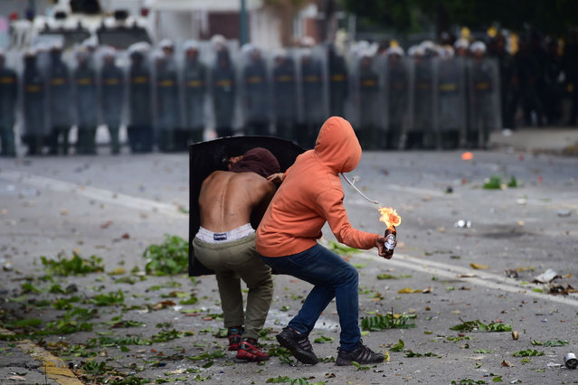 An anti-government activist prepares to throw a Molotov cocktail at members of the National Guard during a 48-hour general strike called by the opposition, in Caracas on July 26, 2017. Venezuelans began blocking off deserted streets Wednesday as the opposition launched a 48-hour general strike aimed at thwarting embattled President Nicolas Maduro's controversial plans to rewrite the country's constitution. (Photo by Ronaldo Schemidt/AFP Photo)
