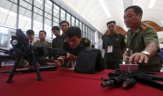 A commune policeman (C) demonstrates an Israeli-made CornerShot rifle during celebrations to commemorate the 70th anniversary of the establishment of the Vietnam Public Security police force at the National Convention Center in Hanoi August 18, 2015. (Photo by Reuters/Kham)