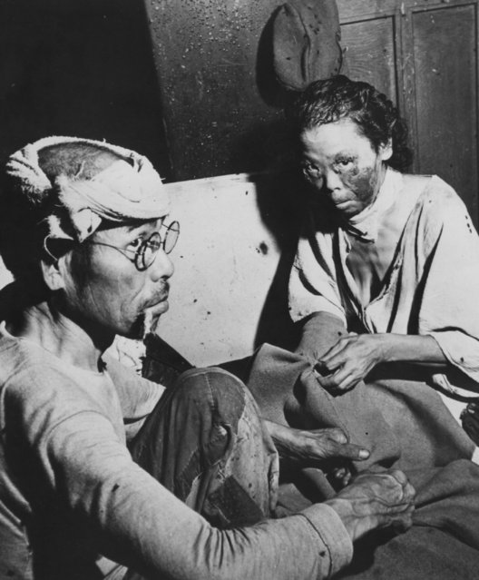 Victims of the atomic blast sit in a makeshift hospital in a damaged bank building in the centre of Hiroshima.   (Photo by Keystone/Getty Images)