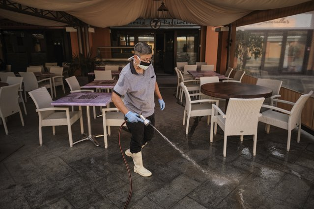 A staffer wearing a mask cleans the terrace of a shopping mall in La Caleta, in the Canary Island of Tenerife, Spain, Wednesday, February 26, 2020. Worries over the ever-expanding economic fallout of the COVID-19 crisis multiplied, with factories idled, trade routes frozen and tourism crippled, while a growing list of countries braced for the illness to claim new territory. Even the Olympics, five months away, wasn't far enough off to keep people from wondering if it would go on as planned. (Photo by AP Photo/Stringer)