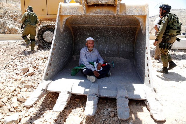 A man sits in the scoop of an Israeli excavator as tries to prevent it from clearing his land during a protest against Jewish settlements, near the village of Deir Qaddis near the West Bank city of Ramallah July 13, 2016. (Photo by Mohamad Torokman/Reuters)