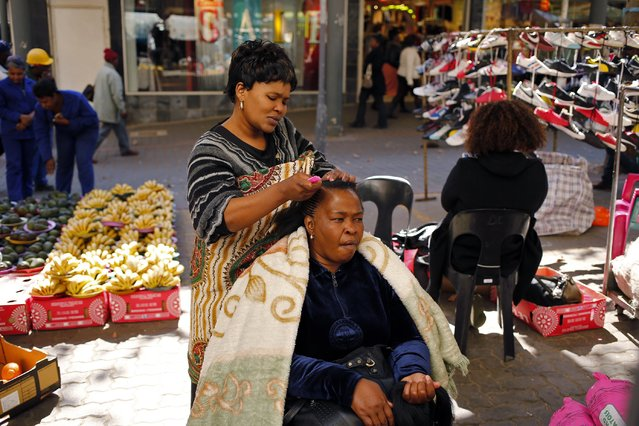 Hairdresser braids the hair of a client in downtown Johannesburg. The French cosmetics giant L'Oreal this year opened what it billed as South Africa's first multi-ethnic styling school, training students of all races on all kinds of hair, something that would have been unthinkable before the end of apartheid in 1994. (Photo by Siphiwe Sibeko/Reuters)