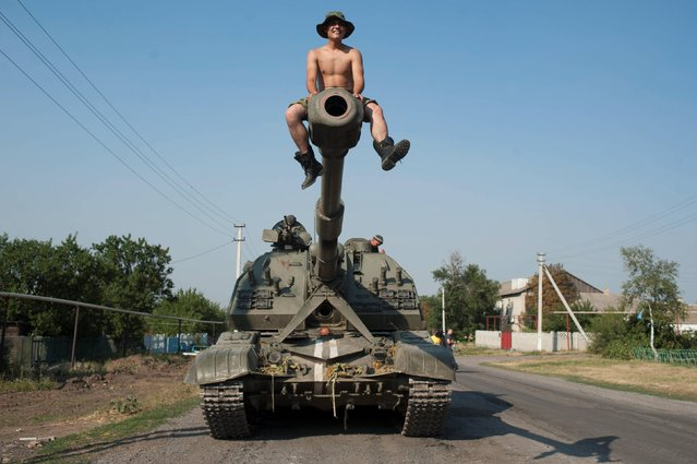 In this photo taken Thursday, August 14, 2014, a Ukrainian soldier sits atop of a self-propelled gun as an army column of military vehicles prepares to roll to a frontline near Illovaisk, Donetsk region, eastern Ukraine. Ukrainian forces have stepped up efforts to dislodge the separatists from their last strongholds in Donetsk and Luhansk and there was more heavy shelling overnight. (Photo by Evgeniy Maloletka/AP Photo)