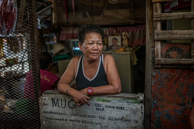 Rosita Opiasa, 59, in her home in Navotas's Market 3 shanty town. Her son, Jayson Rivera, 32, was killed in the drugs war. She still supports Duterte, which is rare in Market 3. Rivera's photograph can be seen in the background. Opiasa runs this corner shop, where she sells single cigarettes or various small bottles of shampoo and detergent because her customers can't afford larger sizes. (Photo by James Whitlow Delano/Funded by the Pulitzer Center on Crisis Reporting/The Guardian)