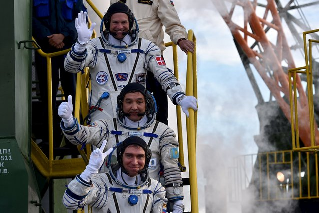 Kazakhstan's cosmonaut Aydyn Aimbetov (C), Russian cosmonaut Sergei Volkov and Denmark's astronaut Andreas Mogensen from the European Space Agency (top) wave as they board the Soyuz TMA-18M spacecraft at the Russian-leased Baikonur cosmodrome early 7 September 2, 2015. (Photo by Kirill Kudryavtsev/Reuters)