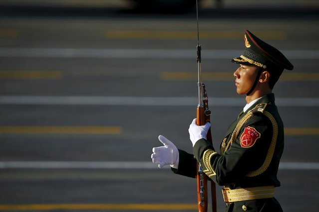 A soldier of the People's Liberation Army (PLA) of China holds his weapon at the Tiananmen Square before a military parade to mark the 70th anniversary of the end of World War Two, in Beijing, China, September 3, 2015. (Photo by Damir Sagolj/Reuters)